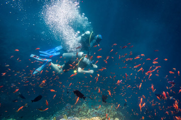 Scuba instructor diving with student near coral reef in Red sea