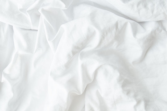 White wrinkled fabic texture,Close up unmade bed sheet in the bedroom after night sleep Soft focus