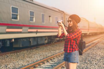 beautiful young asian girl traveling alone shoot camera enjoying at train station.