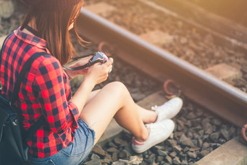 beautiful young asian girl traveling alone shoot camera enjoying at train station.
