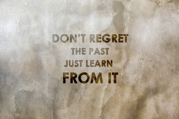 """Inspirational positive quote """"Don't regret the past, just learn from it."""" with cement wall background."""