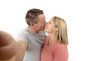 young beautiful happy and attractive romantic couple with husband and wife or girlfriend and boyfriend taking selfie self portrait photo