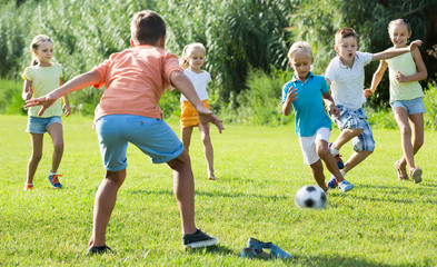 Group of friendly kids playing football together on green lawn in park
