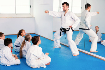 Coach showing new martial moves to children in karate class