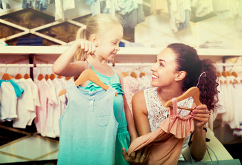 mother brunette with daughter buying kids clothes