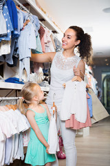 Mother with small daughter girl  buying clothes