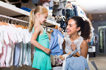 young woman and girl in clothes store.