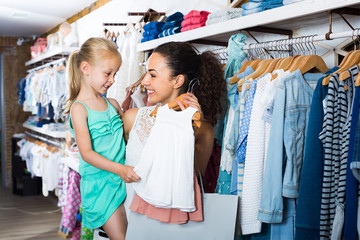 mother brunette with daughter buying baby pajamas in kids section