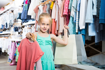 portrait of  girl standing in kids clothes store with shopping bags