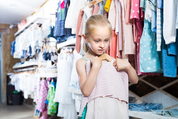 Little girl holding new dress in hands in boutique