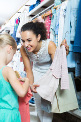 Mother with daughter buying dress