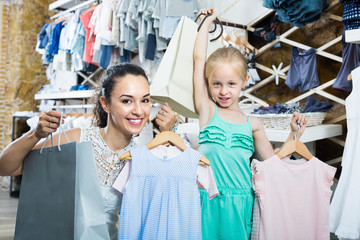 Female customer with small girl holding clothes