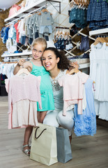 Positive woman with smiling girl holding clothes