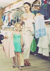 Cheerful woman with smiling girl choosing clothes