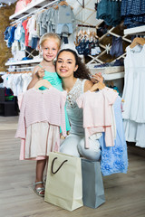 young smiling mother with happy daughter in shop