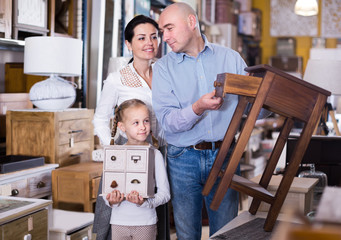Happy family  with small daughter looking nightstand