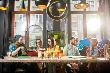 Group of friends dressed casually talking and sitting together at the big table in the modern cafe interior