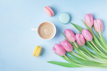 Spring tulip flowers, colorful macaroons and coffee on blue pastel table top view. Beautiful breakfast on Mothers or Womans day. Flat lay.