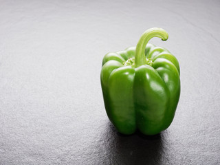 Green bell pepper or capsicum over dark black background