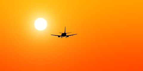 The black silhouette of a passenger airplane flying towards the sun.
