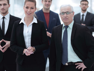 serious businessman and business woman on the background of the office staff.