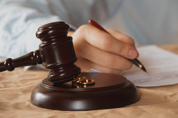 Closeup of male hand signing divorce papers.