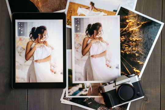 Printed wedding photos with the bride, a vintage black camera and a black tablet with a picture of bride