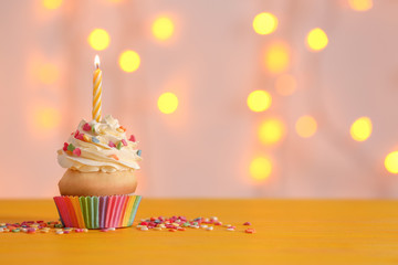 Birthday cupcake with candle on table against blurred lights