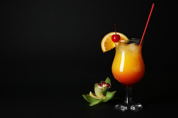 Glass of Sex on the Beach cocktail against dark background
