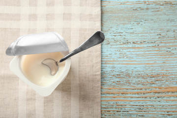 Plastic cup with yogurt on wooden background