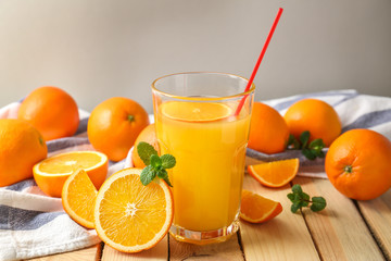Glass of fresh orange juice with fruit on wooden table