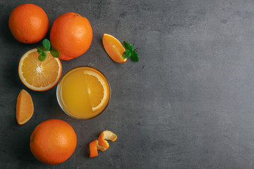 Beautiful composition with fresh orange juice and fruit on grey background