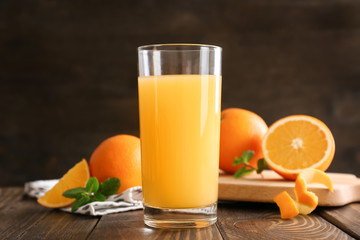 Glass of fresh orange juice on wooden table