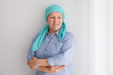 Mature woman with cancer in headscarf on light background