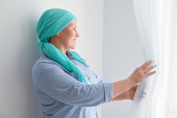 Mature woman with cancer standing near window indoors