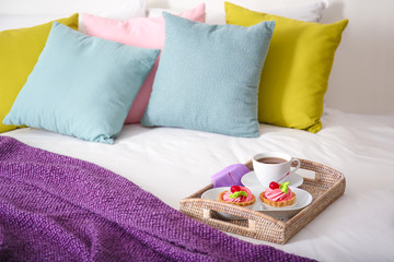 Tray with tasty breakfast on comfortable bed at home