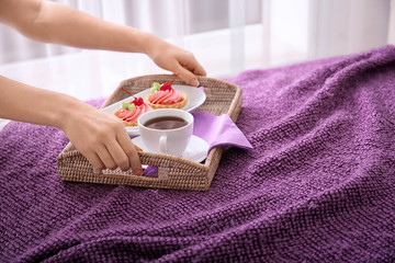 Woman putting tray with tasty breakfast on comfortable bed at home