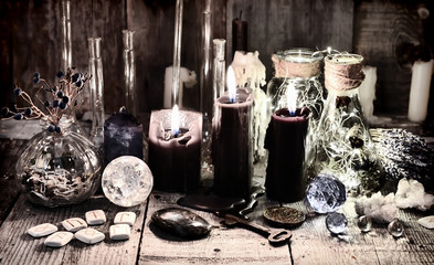 Black candles with runes, crystals, old key, healing herbs and magic ritual objects Halloween, occult, esoteric and wicca concept. Vintage background