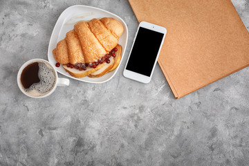 Tasty croissant with cup of coffee and mobile phone on table