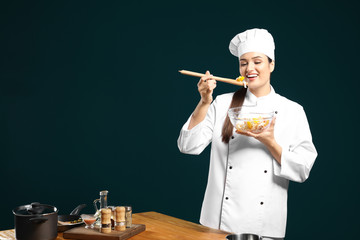 Beautiful female chef tasting salad on color background