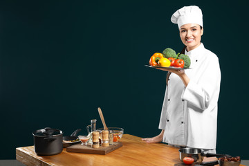 Beautiful female chef holding plate with vegetables near table on color background