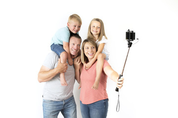 lovely young couple taking selfie photo self portrait with stick and mobile phone carrying son and daughter on shoulders posing happy smiling
