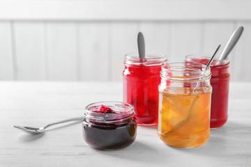 Jars with sweet jams on table