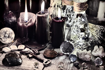 Black candles, crystals and stones, ancient runes, key and ritual bottles on witch table Halloween, occult, esoteric and wicca concept. Vintage background