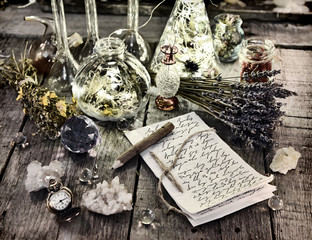 Witch manuscript with pencil, magic bottles, crystals, old clock and lavender flowers on planks. Halloween, occult, esoteric and wicca concept. Vintage background