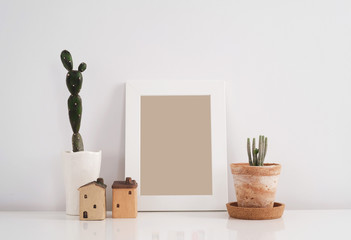 Scandinavian style hipster room interior. Cactus in clay pot with blank photo frame background.