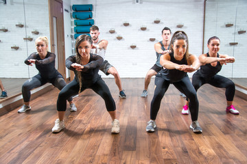 Group of young fit women and man exercising together in fitness club.