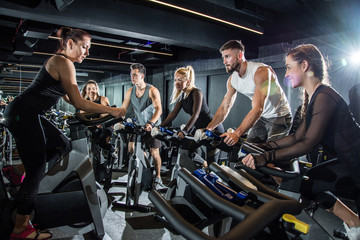 Female fitness instructor leading spinning class in gym.