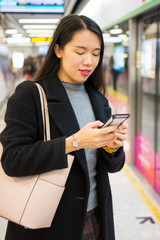 Girl using phone while waiting for the metro
