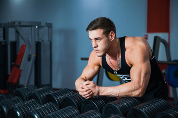 Fit male athlete getting ready for dumbbell workout. Handsome man at fitness gym take rest and breathe. Fitness, bodycare and active lifestyle concept.